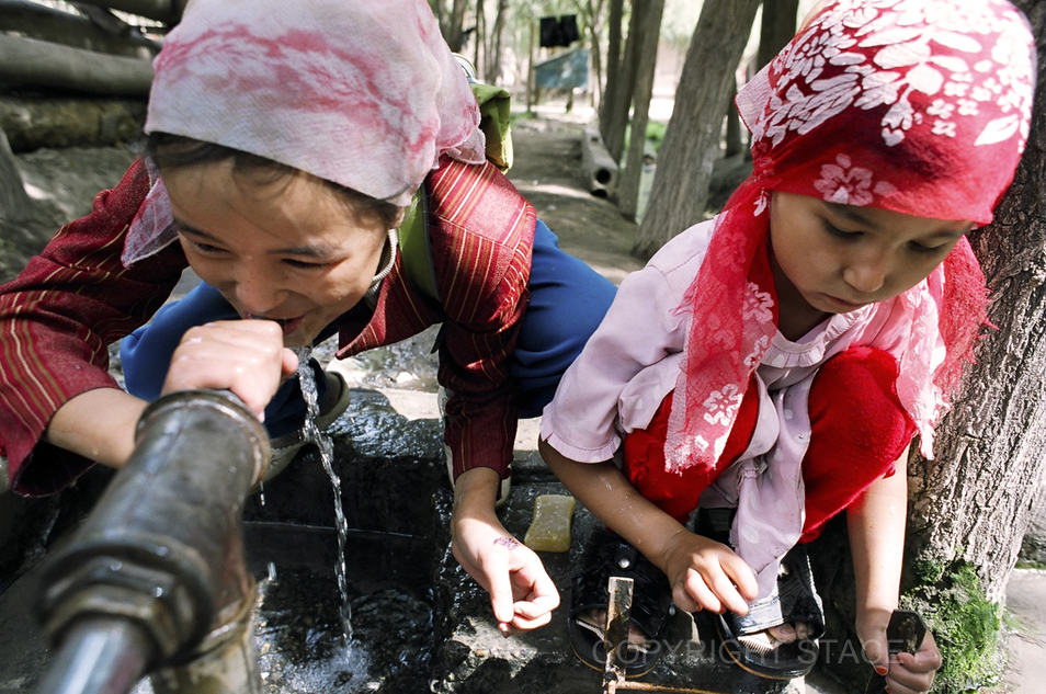 Uighur girls play near a local water source in Kashgar's Old Town after school. Many of the homes in the Old Town lack adequate plumbing.  Residents come to this communal area to fetch water and do laundry.
