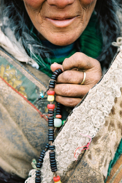 A Tibetan woman holds prayer beads in a town near Xiahe in Qinghai Province, China.