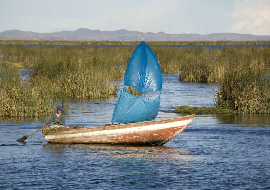 An Uros man uses a tarp for a sail on Lake Titicaca in Peru. The Uros people live on floating islands made of totora reeds that grow in the lake. The reeds are harvested as building material and as a food source.