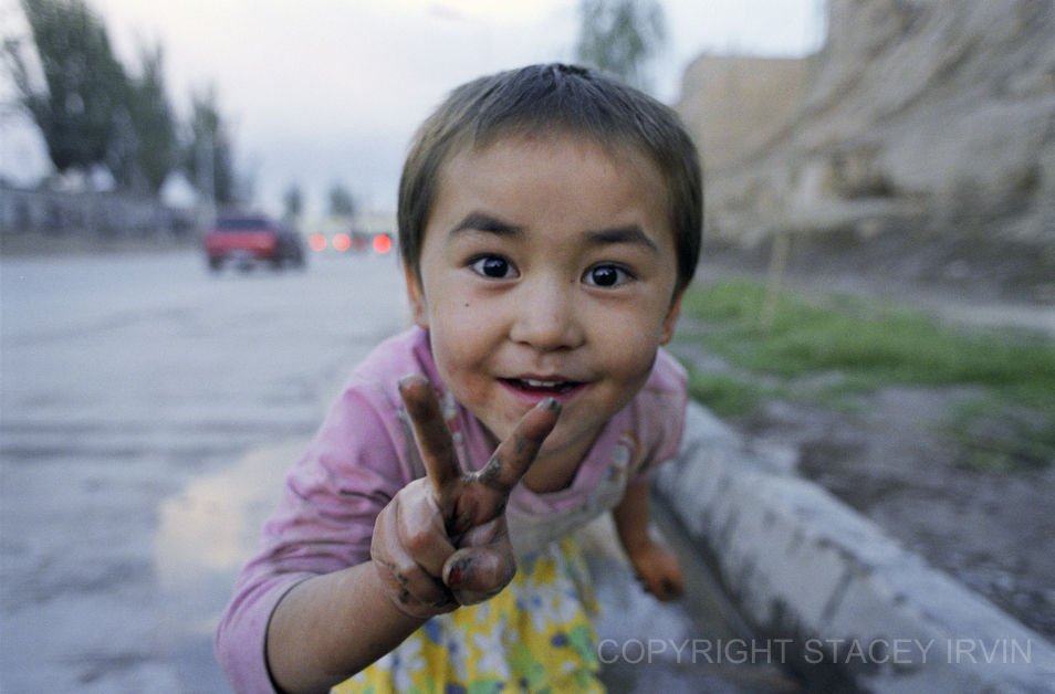 Interrupted while playing in a roadside puddle near Kashgar's Old Town, this Uighur girl shows a spontaneous and enthusiastic sign for peace.
