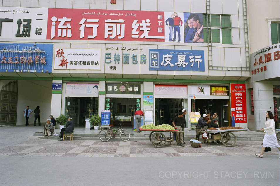 Uighurs sell grapes and dates in front of modern Chinese shops on the edge of the Han part of town in