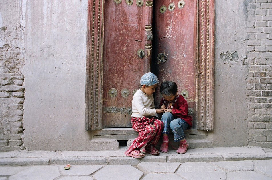 A little girl carefully paints her friend's nails while sitting in a doorway in the Uighur Old Town area of Kashgar. 